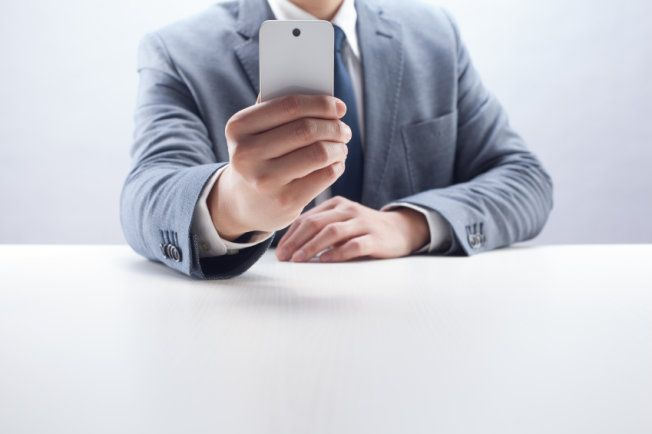 Stock image of a man in a suit using a camera phone.