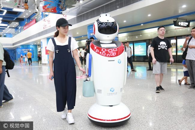 A smart robot helps a passenger carry a handbag at Ningbo Railway Station in Zhejiang Province, on August 7, 2017. The smart robot has been activated to help passengers search for ticket fares, print route maps and carry their luggage. [Photo: VCG]