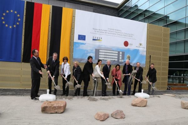 With German and EU flags in the background, representatives from the sponsoring authorities are using shovels to throw soil to the ground where the building is going to be constructed.