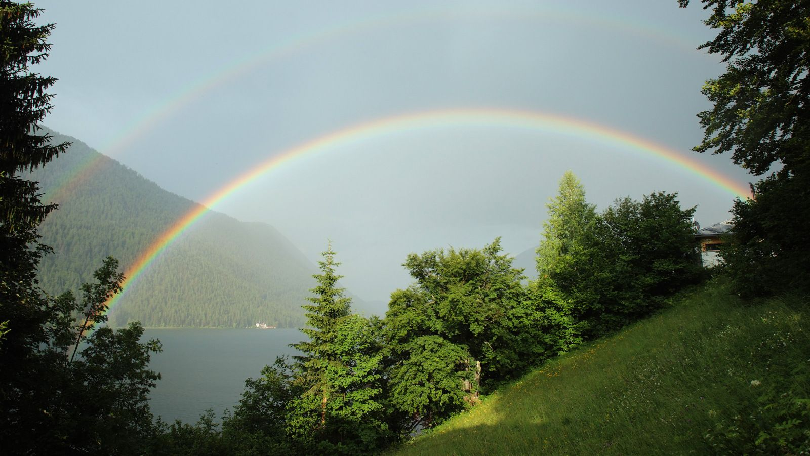 A double rainbow appears above Lake Weissensee in Naggl in Austria's southern Carinthia province July 10, 2013. REUTERS/Heinz-Peter Bader  (AUSTRIA - Tags: TRAVEL ENVIRONMENT SOCIETY)  - RTX11J42